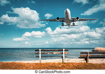Beautiful airplane and wooden bench at the sea. Landscape...