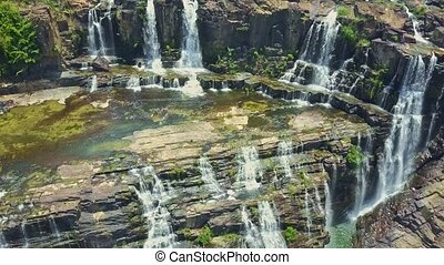 Drone Hangs Close to Waterfalls Flowing from Cliffs - drone...
