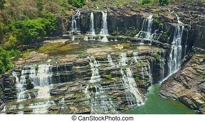 Flycam Hangs above Narrow Waterfalls Running from Rocks -...