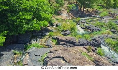 Drone View of Streams Turning into Waterfalls against Rocks...
