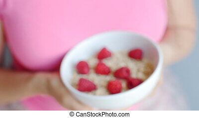Woman's hands holding a cup with organic oats and berries -...