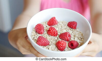 Woman's hands holding a cup with organic oats and berries
