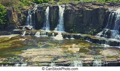 Flycam Shows View of Waterfalls against Rocks in Tropics -...