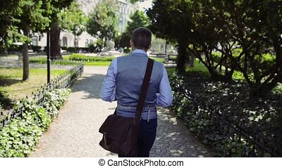 Mature businessman walking in the city park. Rear view. -...