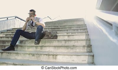 Mature businessman with lunch sitting on stairs in the city....
