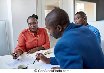 Young African business colleagues discussing paperwork in an office