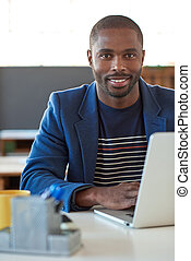 Confident African businessman working on a laptop in an office