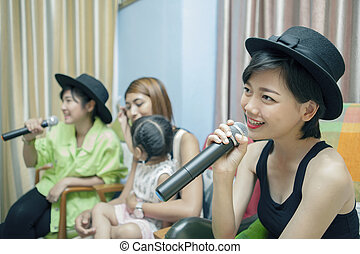 beautiful asian younger woman singing karaoke song at home ,family relaxing and happy time