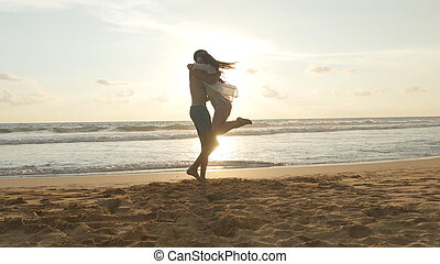 Young couple is running on the beach, man hug and spin...