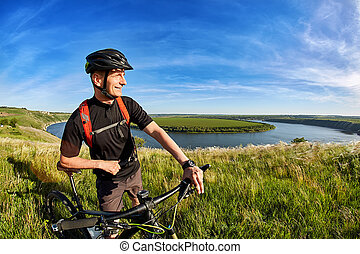 Attractive cyclist standing on the hill with mountain...