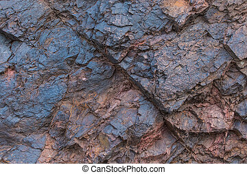 Iron ore texture close up - natural minerals in the mine. Stone texture of open pit. Extraction of minerals for heavy industry - the texture of the rock containing iron ore and copper.