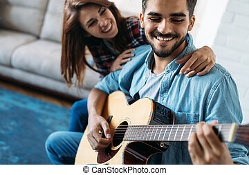 Young handsome man playing guitar for his girlfriend