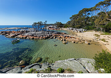 Turquoise waters rippled, lichen growing on granite rocks -...