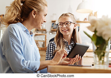 Cheerful mother and daughter discussing a video - Precious...