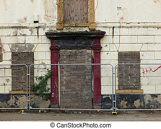 derelict abandoned house on the street with barriers in...