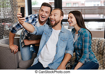 Bright admirable guy enjoying fun time with his friends -...