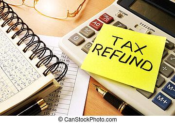 Tax refund. - Memo stick with words tax refund.
