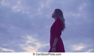 Young woman in red dress against cloudy sky - Gold time...