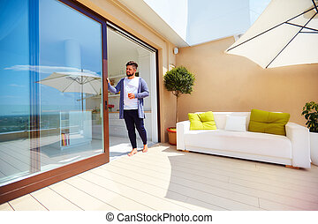 handsome man enjoys life on rooftop terrace, with open space kitchen and sliding doors