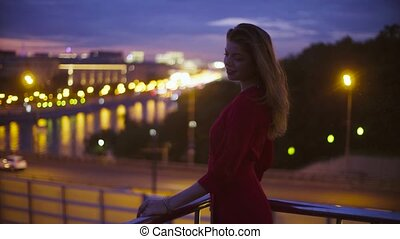Young woman in red dress is standing near parapet - Gold...