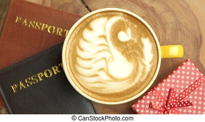 Coffee, passports and present. Gift box on wooden board.