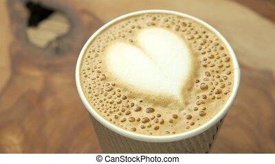 Heart latte art. Light coffee foam, blurred background....