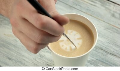 Hand making latte art clock. Paper cup with frothy coffee....