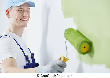 Happy man painting a wall - Happy and young man is painting...