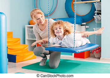 Boy on therapy swing - Woman helping a smiling boy to...