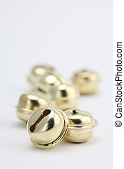 Gold jingle bells - Close-up of gold jingle bells on white...