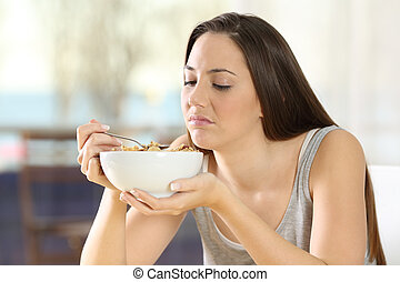Disgusted woman eating cereals with bad taste at home