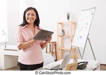 Joyful pregnant asian woman standing in the office