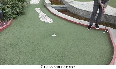 Boy playing in minigolf in summer day