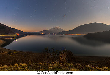 Shooting star during starry night over Mt. Fuji at Motosuko...