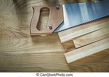 Hacksaw wooden planks on wood board construction concept.