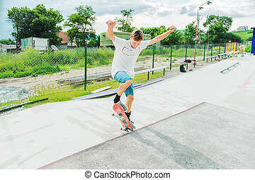 A boy in a skate park doing a trick on a skateboard
