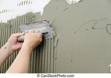 Tilers hands are putting an adhesive.