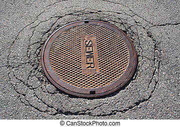 Manhole cover - Rusted manhole sewer cover on cracked...