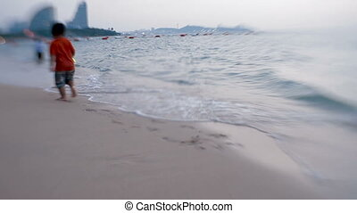 Sea surf. Waves erase kid's footprints on the sand. Pattaya,...