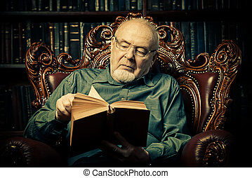flipping the pages - An old intelligent man reading a book...