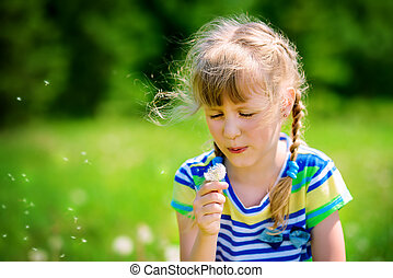 blow off a dandelion - Funny little girl with dandelions in...