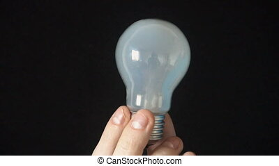 young man holding a light bulb against a black background