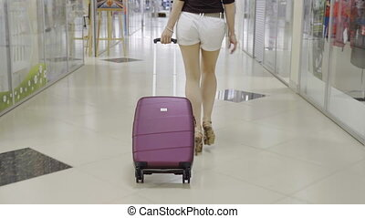 Woman is dragging a suitcase