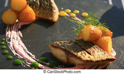 A dish of haute cuisine. close-up. Fish with young potatoes....