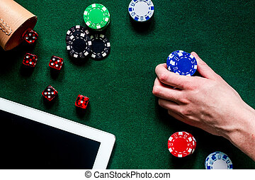 Compulsive gambling. Hand with poker chip and the dice nearby keyboard on green table top view copyspace