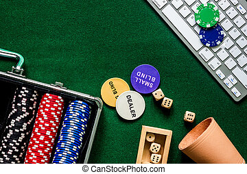 Compulsive gambling. Poker chips and the dice nearby keyboard on green table top view copyspace