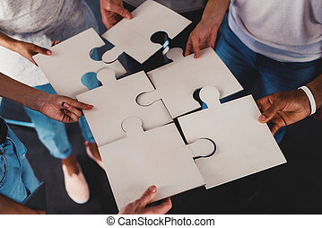 Team of young businessmen combine pieces of puzzle. Concept of integration and partnership