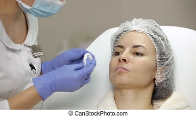 Beautician applies anesthetic cream on t lips of patient...