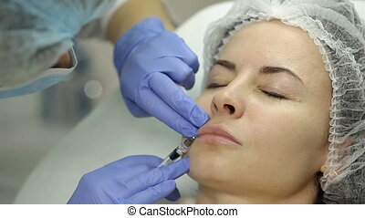 Lip augmentation in beauty salon. Beautician makes injection...