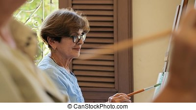 Elderly Woman Practicing Her Hobby Painting In Art Class -...